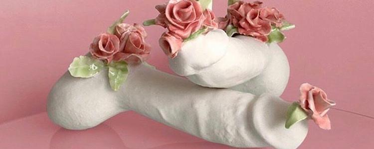 bild av två penisar gjorda av keramik, täckta av blommor.