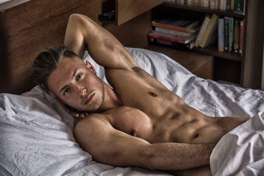 en man ligger i sängen och njuter av en prostatavibrator, som dock ej syns på bild