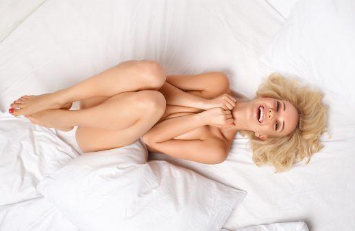 Blond tjej ligger naken i sängen